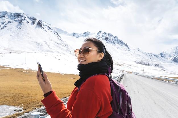 Jeune femme avec un smartphone dans les montagnes de l'himalaya Photo Premium
