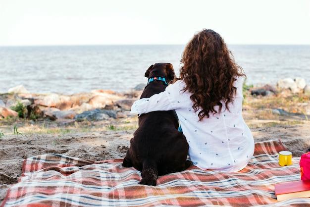 Jeune femme avec son chien à la plage Photo gratuit