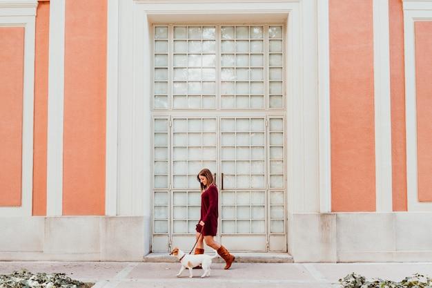 Jeune femme et son joli chien jack russell marchant près de la ville Photo Premium