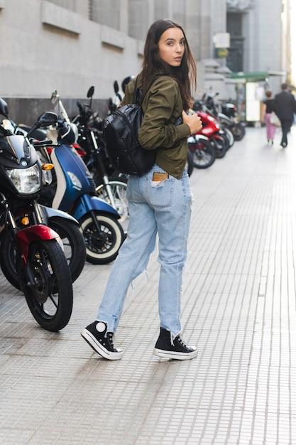 Jeune femme avec son sac à dos, marchant sur le trottoir Photo gratuit