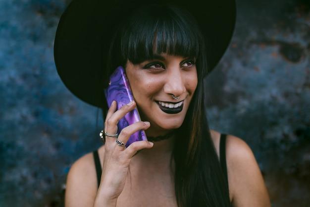 Jeune femme de sorcière halloween heureuse à l'aide d'un téléphone intelligent. beauty witch lady avec la bouche noire dans l'obscurité, coiffée d'un chapeau de sorcière. Photo Premium