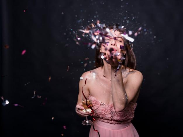 Jeune femme soufflant des confettis Photo gratuit