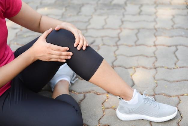 Jeune femme souffrant d'une blessure au genou ou à la rotule lors d'une séance d'entraînement en plein air sur le sol. Photo Premium