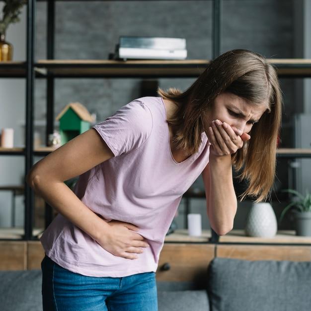 Jeune femme souffrant de maux d'estomac souffrant de nausée Photo gratuit