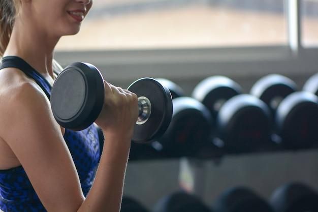 Jeune femme soulever des haltères, concept de fitness gym. Photo Premium