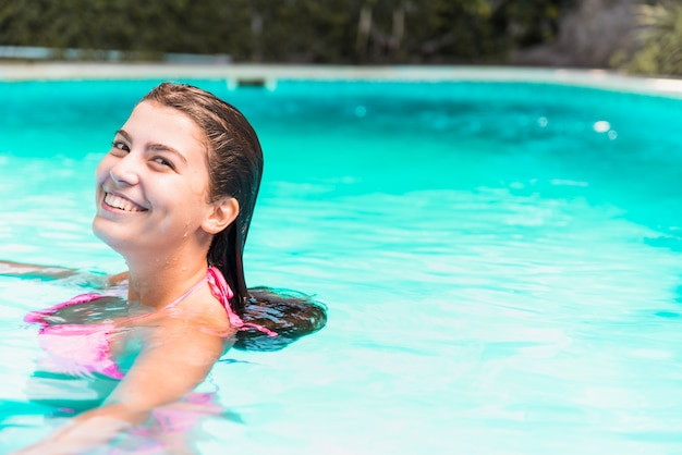 Jeune femme souriante en bikini dans la piscine Photo gratuit