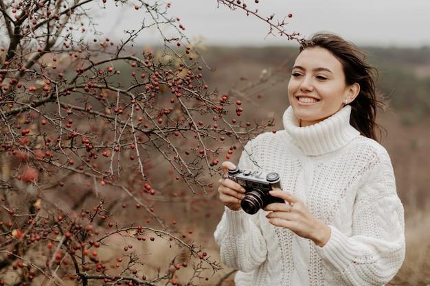 Jeune femme souriante avec caméra Photo gratuit