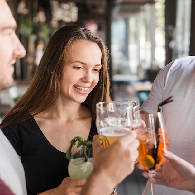 Jeune femme souriante, faire griller des boissons avec ses amis Photo gratuit