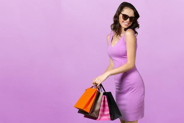 Jeune femme souriante heureuse avec des sacs à provisions Photo Premium