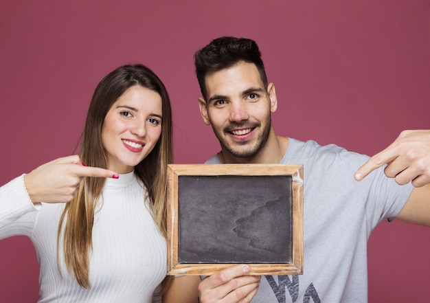 Jeune femme souriante et homme positif pointant sur le cadre photo Photo gratuit