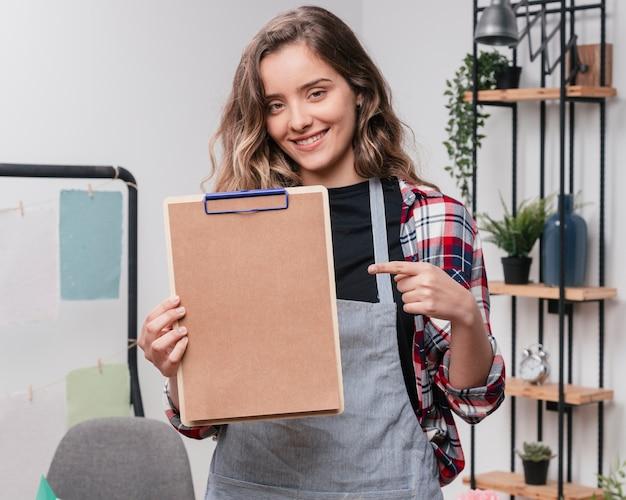 Jeune, femme souriante, pointage, index, presse-papiers Photo gratuit