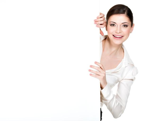 Jeune Femme Souriante à La Recherche D'une Bannière Vierge Blanche - Sur L'espace Blanc Photo gratuit