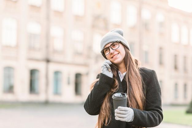 Jeune femme souriante avec tasse parler sur smartphone dans la rue Photo gratuit