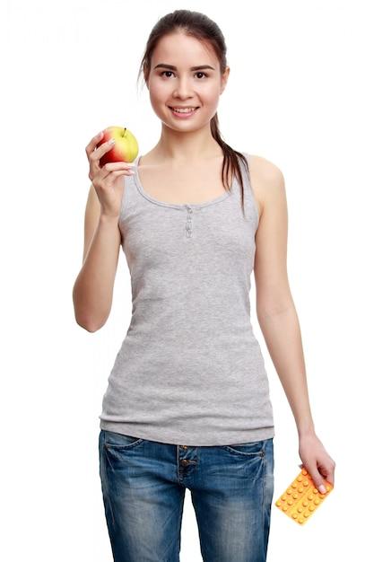 Jeune femme souriante tenant la pilule dans une main et pomme dans l'autre Photo Premium