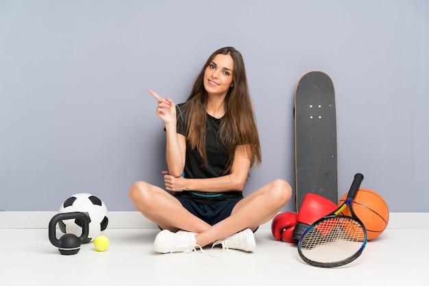 Jeune femme sportive assis sur le sol, pointant le doigt sur le côté Photo Premium