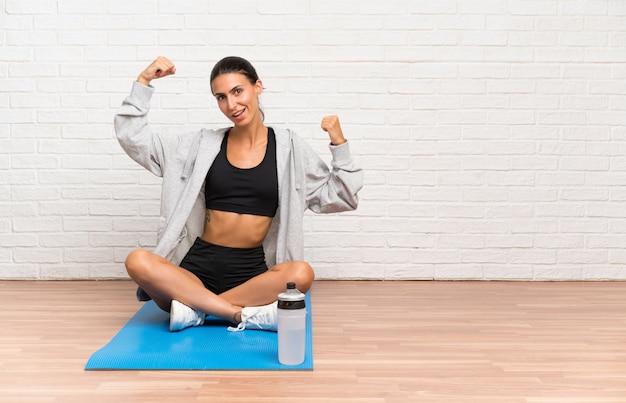 Jeune femme sportive assise sur le sol avec un tapis célébrant une victoire Photo Premium