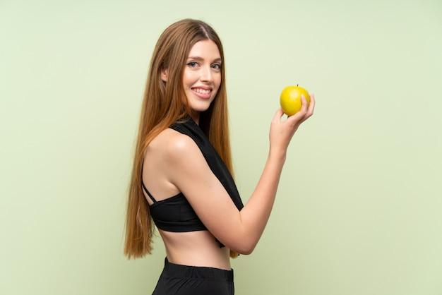 Jeune femme sportive au vert isolé avec une pomme Photo Premium