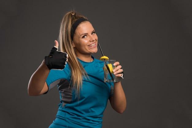 Jeune Femme Sportive Ayant Une Boisson énergisante Et Fait Le Pouce Vers Le Haut. Photo gratuit