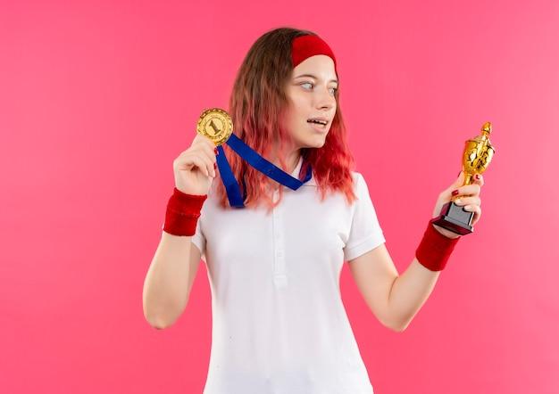 Jeune Femme Sportive En Bandeau Avec Médaille D'or Autour De Son Cou Tenant Le Trophée En Le Regardant Heureux Et Sorti Debout Sur Le Mur Rose Photo gratuit