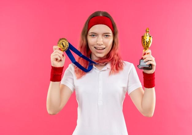Jeune Femme Sportive En Bandeau Avec Médaille D'or Autour De Son Cou Tenant Le Trophée Avec Smilie Sur Le Visage Debout Sur Un Mur Rose Photo gratuit