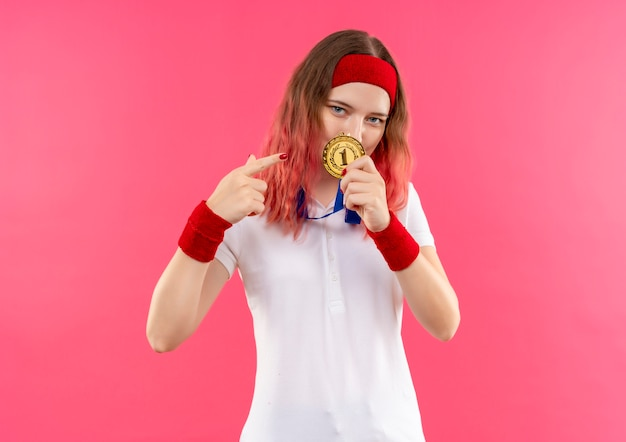 Jeune Femme Sportive En Bandeau Montrant La Médaille D'or Pointant Avec Le Doigt Sur Elle à La Confiance Debout Sur Le Mur Rose Photo gratuit