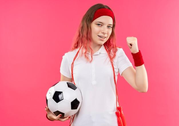 Jeune Femme Sportive En Bandeau Tenant Un Ballon De Football Serrant Le Poing Heureux Et Sorti Debout Sur Un Mur Rose Photo gratuit