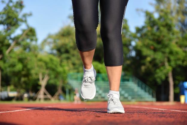 Jeune femme sportive court sur la piste du stade le matin Photo Premium