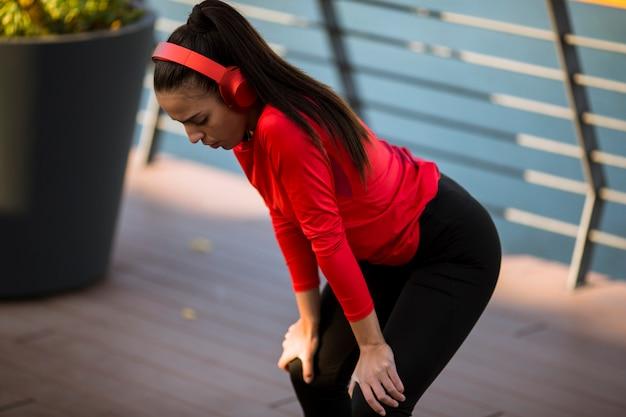 Jeune femme sportive avec des écouteurs prenant la pause après une course en milieu urbain Photo Premium
