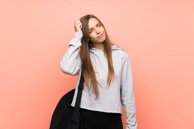 Jeune femme sportive isolée rose ayant des doutes et avec une expression du visage confuse Photo Premium