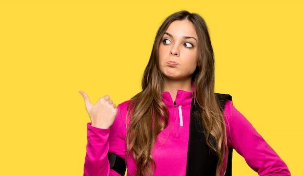 Jeune femme sportive malheureuse et pointant sur le côté isolé fond jaune Photo Premium