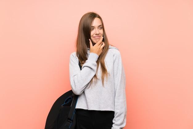 Jeune femme sportive sur un mur rose isolé, pensant à une idée Photo Premium