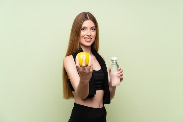 Jeune femme sportive sur un mur vert isolé avec une pomme Photo Premium
