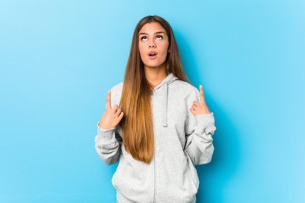 Jeune Femme Sportive Pointant à L'envers Avec La Bouche Ouverte. Photo Premium