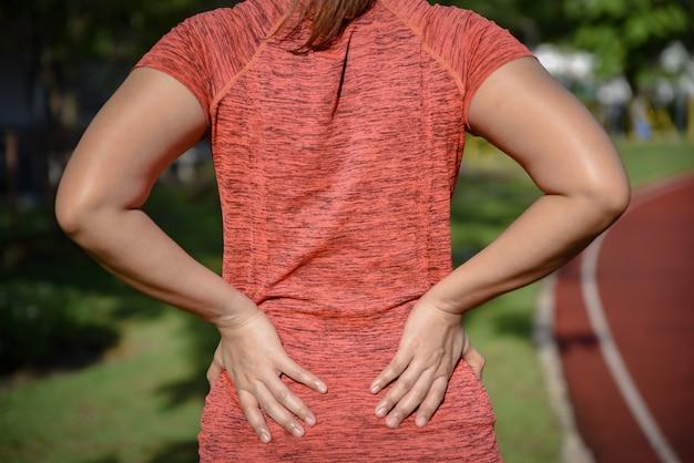 Jeune femme sportive souffrant de maux de dos Photo Premium