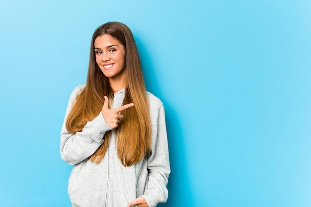 Jeune Femme Sportive Souriante Et Pointant De Côté, Montrant Quelque Chose à L'espace Vide. Photo Premium