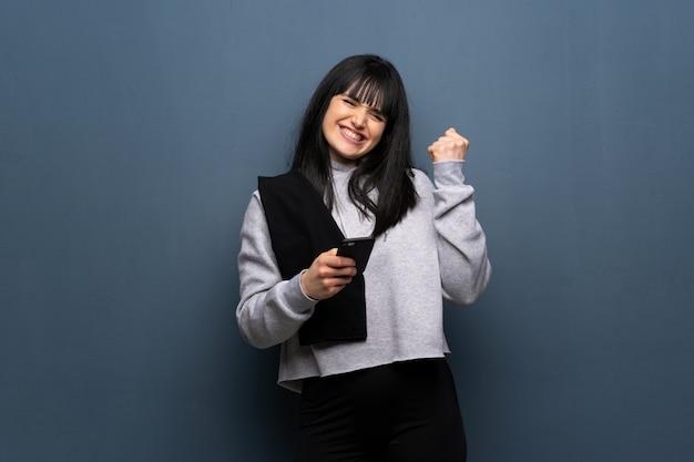 Jeune Femme Sportive Avec Téléphone En Position De Victoire Photo Premium