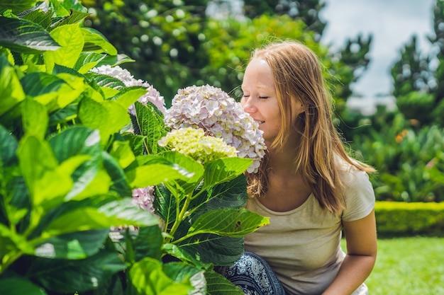 Jeune Femme à La Surface De Fleurs D'hortensia Rose Clair Qui Fleurit Dans Le Jardin Photo Premium