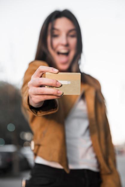 Jeune femme surprise avec une carte en plastique Photo gratuit