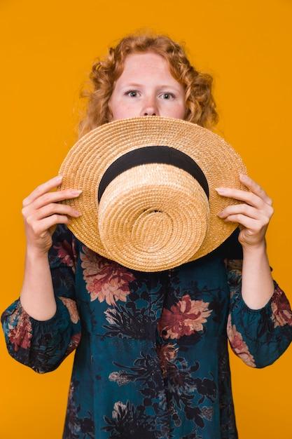 Jeune femme surprise couvrant le visage avec un chapeau Photo gratuit