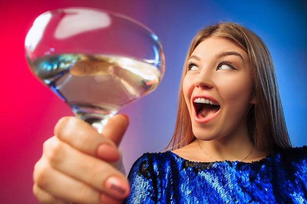 La Jeune Femme Surprise En Tenue De Fête Posant Avec Un Verre De Vin. Visage Mignon Féminin émotionnel. Vue Depuis Le Verre Photo gratuit