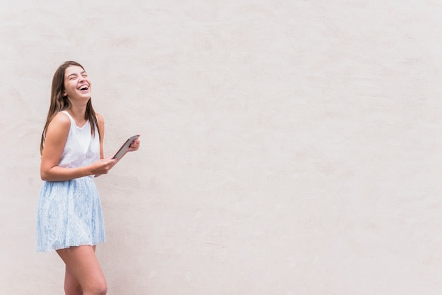 Jeune femme avec tablette en riant sur fond blanc Photo gratuit