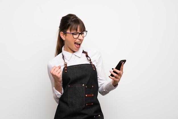 Jeune femme avec tablier avec téléphone en position de victoire Photo Premium