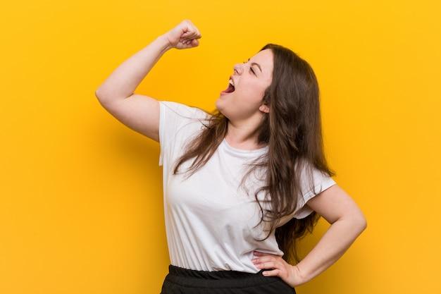 Jeune femme taille plus galbée, levant le poing après une victoire, concept gagnant. Photo Premium