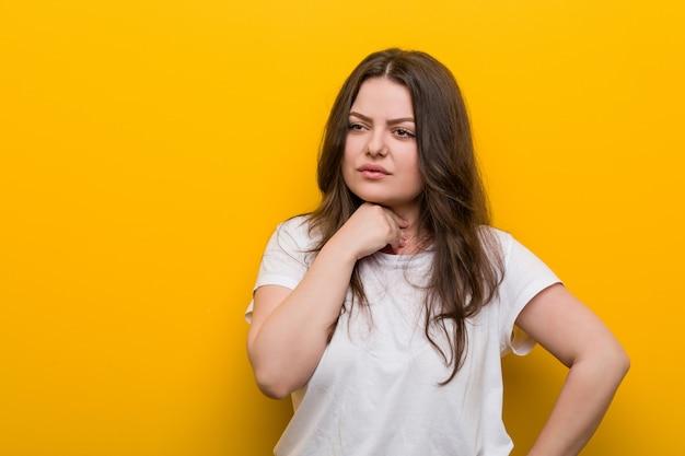 Une jeune femme de taille plus galbée a mal à la gorge à cause d'un virus ou d'une infection. Photo Premium