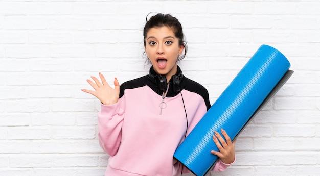Jeune femme avec tapis sur mur de briques blanches avec une expression faciale choquée Photo Premium