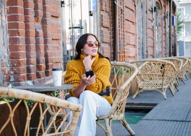 Jeune femme avec une tasse de café en plein air Photo Premium