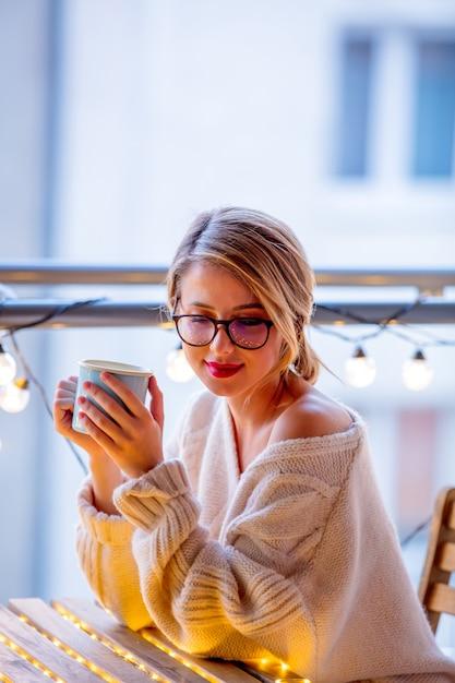 Jeune femme avec une tasse de café près de guirlandes Photo Premium