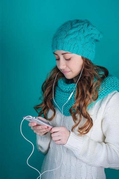 Jeune femme avec un téléphone dans ses mains, écouter de la musique sur des écouteurs Photo Premium
