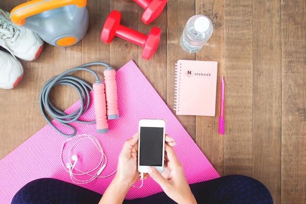 Jeune femme avec un téléphone portable assis près d'haltères sur un tapis d'yoga, vue de dessus. Photo Premium