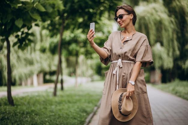 Jeune femme avec un téléphone portable dans le parc Photo gratuit
